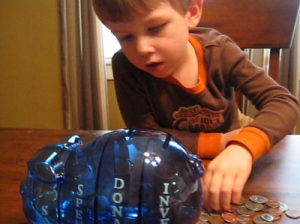 Boy putting money in MSPig - Blogger image